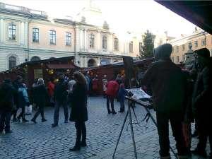 Konstnär med sitt staffli målar Stortorgets Julmarknad