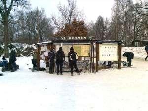 Skidor och skidåkare vid informationstavla